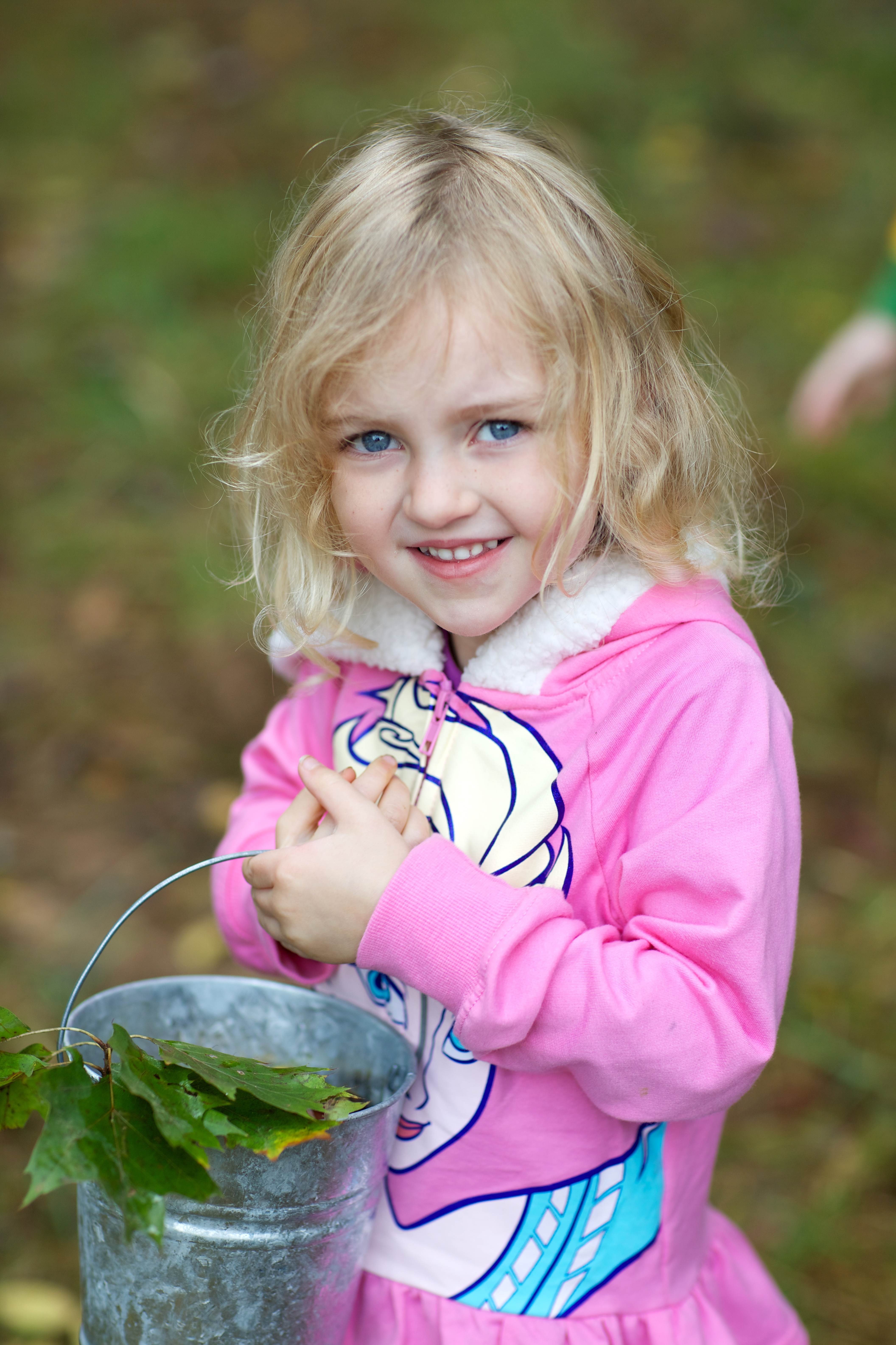 Free photograph; cute, blonde, young, girl, collects, acorns, leaves, bucket