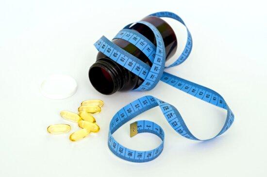 yellow pills, bottle, measuring tape, lose weight