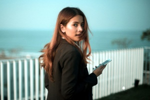 woman looking back, holding smartphone