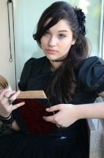 woman holding book, black hair, reading, sitting