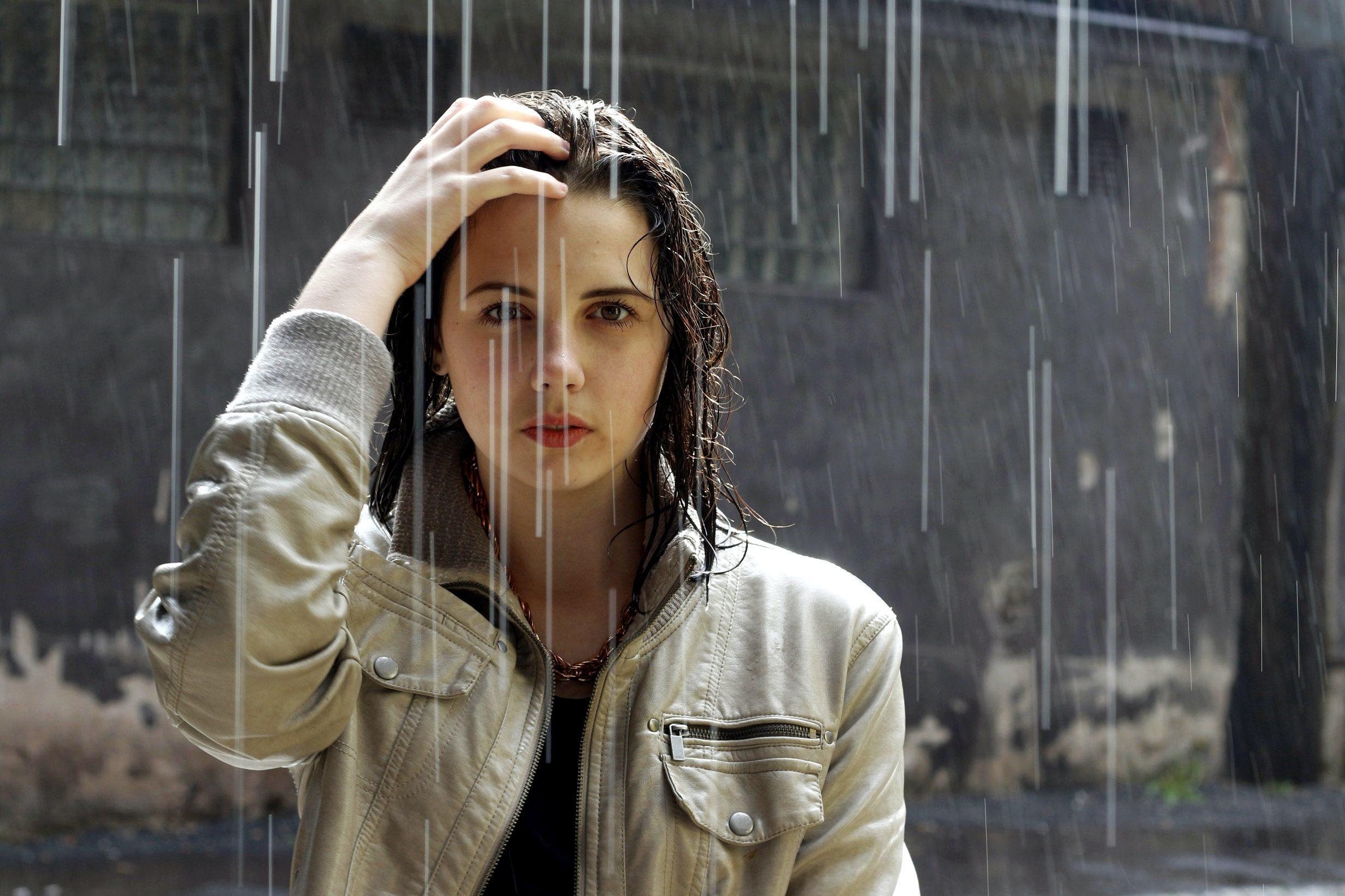 Smiling Caucasian woman standing in rain - Stock Photo