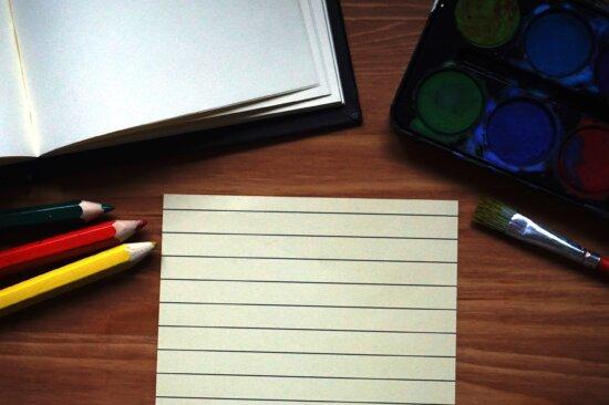 notebook, paper, pencils, paint, paintbrush, wooden table