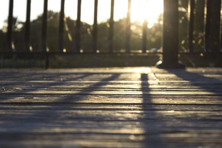 Solen, træ planker, trægulv, skygger, gelænder