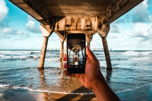 sky, water, waves, beach, photo camera, clouds, dock, fingers, hand