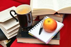 Tazza di caffè, mela, matita, libro