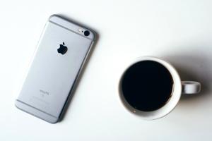 Taza de café, teléfono, mesa
