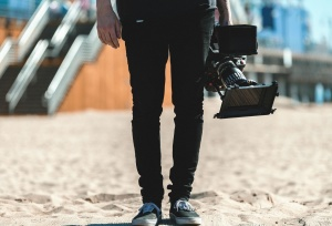 video camera, man, pants, sand
