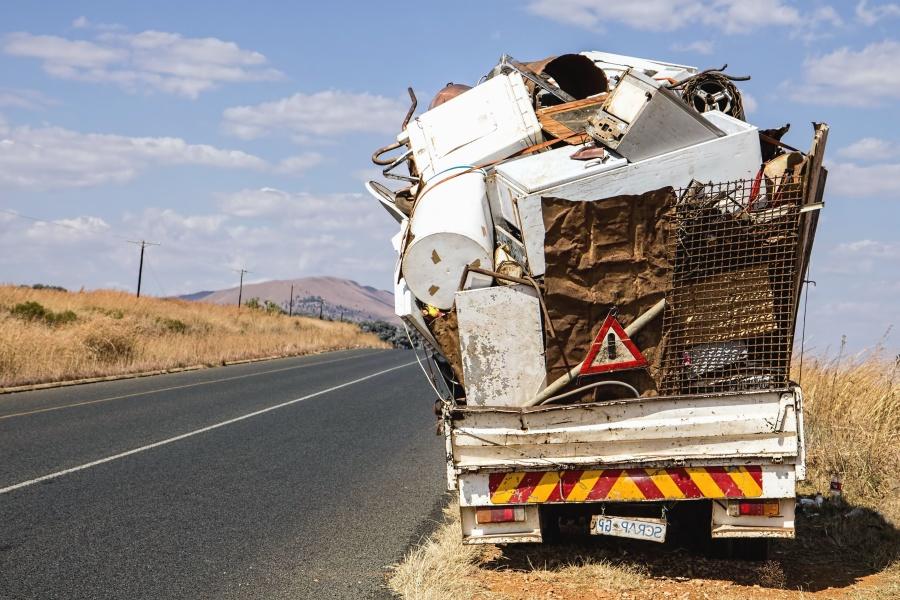 vehicle, trailer, sky, traffic sign, trash, road