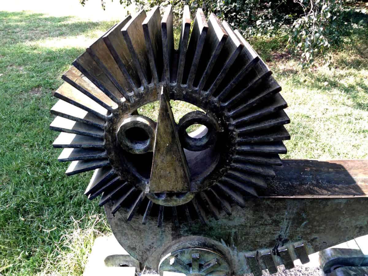 sculpture, object, art, metal, lion, machine, timepiece, gear, mechanism, grass, outdoor