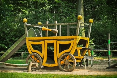 wooden carriage, tree, grass, outdoor, object, vehicle, playground, daylight
