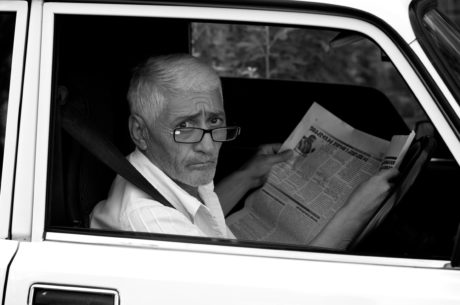 car, car seat, eyeglasses, grandfather, news, newspaper, person, television