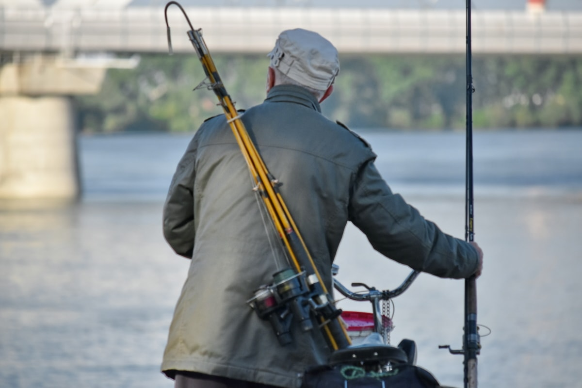 bicycle, fishing gear, fishing license, fishing rod, man, vehicle, outdoors, competition, action, portrait