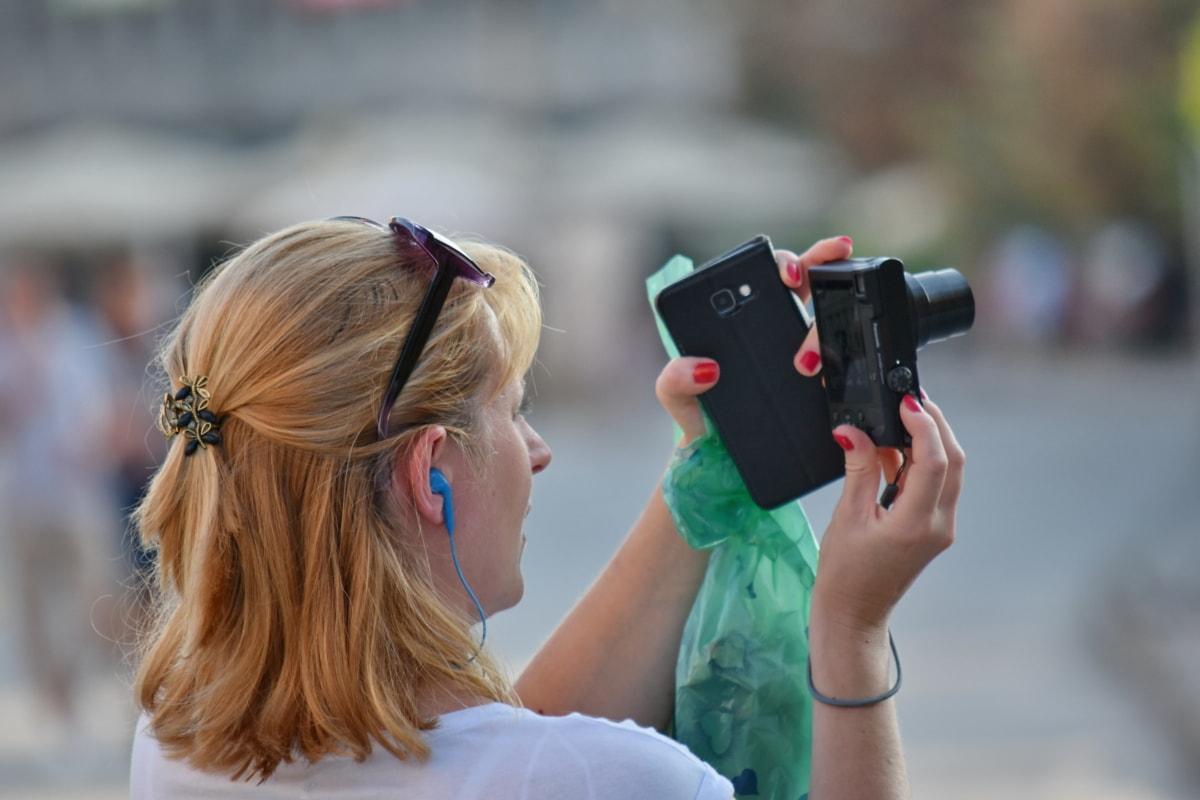 camera, cellphone, tourist attraction, urban area, woman, instrument, people, outdoors, street, fun
