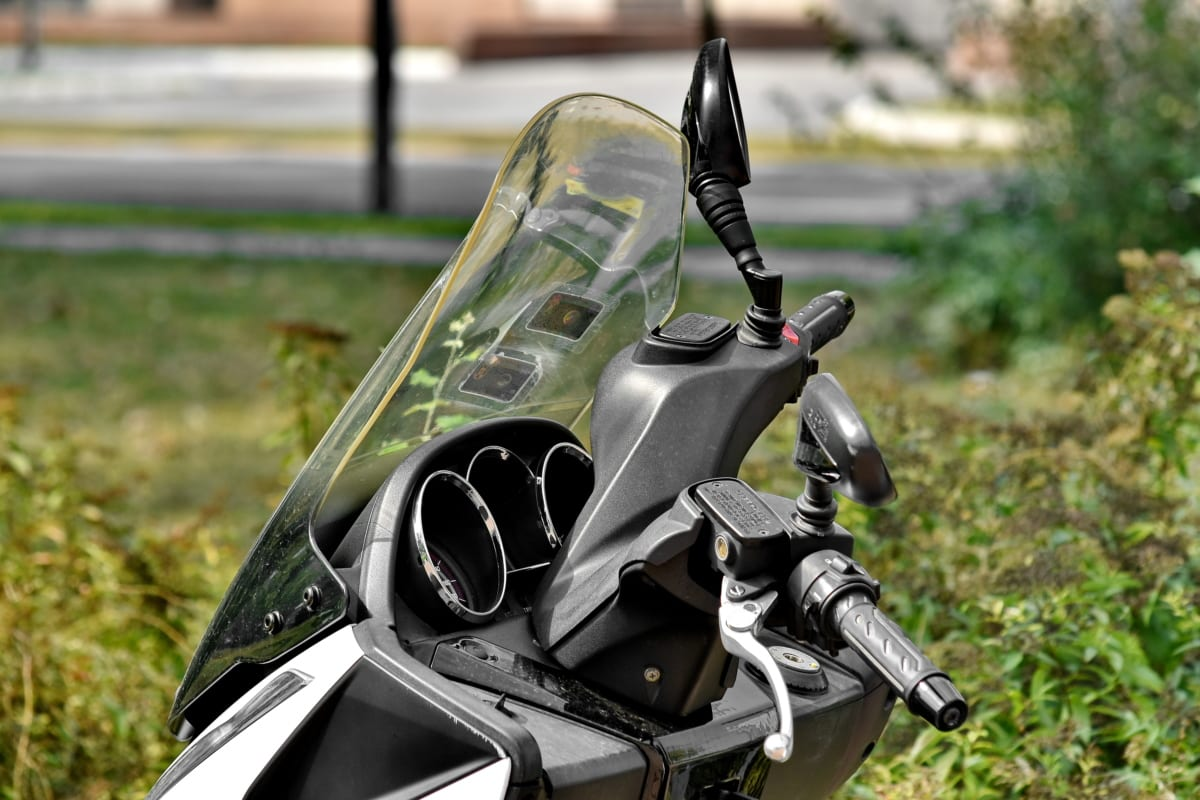 mirror, motorcycle, park, parked, parking lot, urban area, windshield, outdoors, grass, vehicle