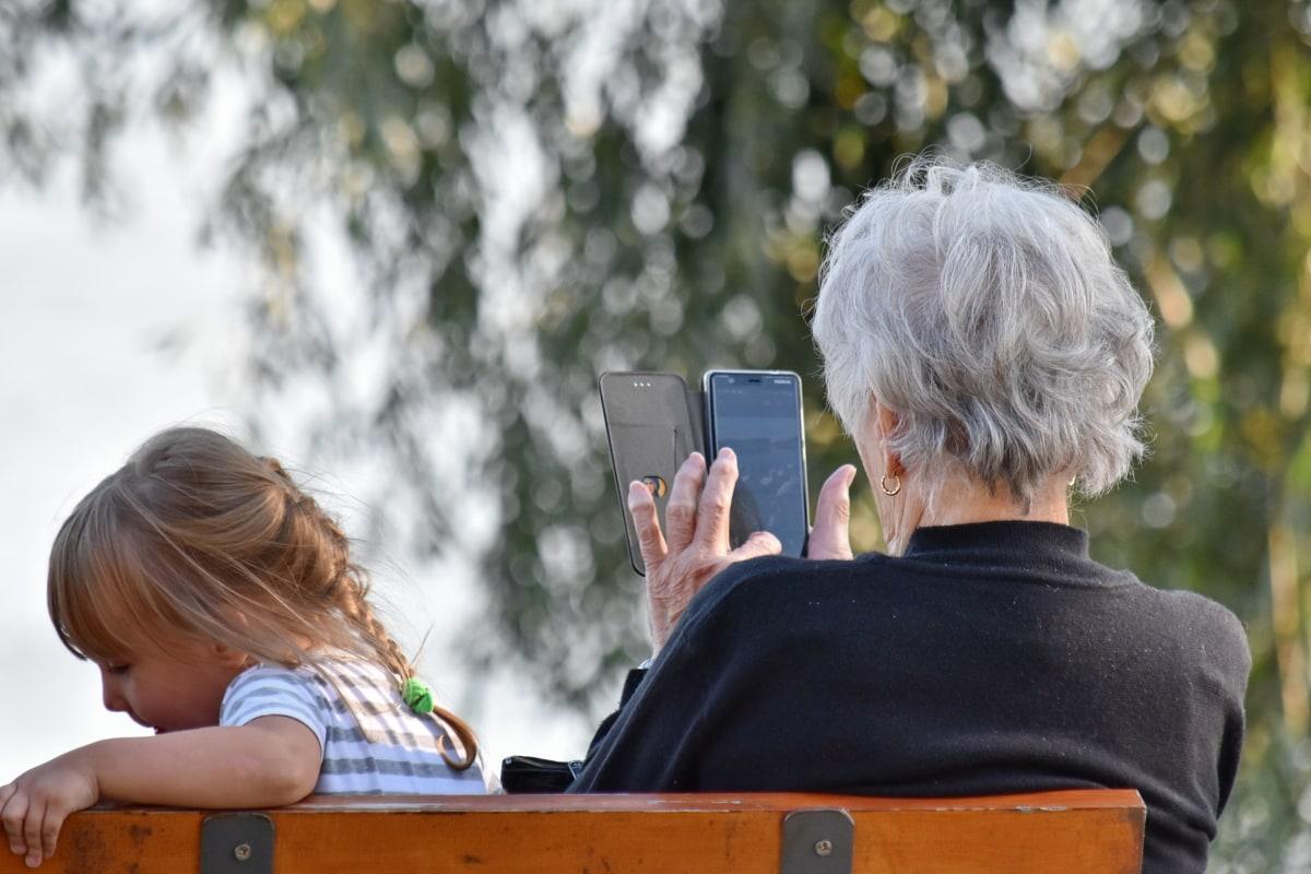 Viihde, lapsenlapsi, tyttärentytär, isoäiti, eloisa soittaa puhelimella, rentoutumista, yhteishenki, ulkona, vapaa-ajan, lapsi