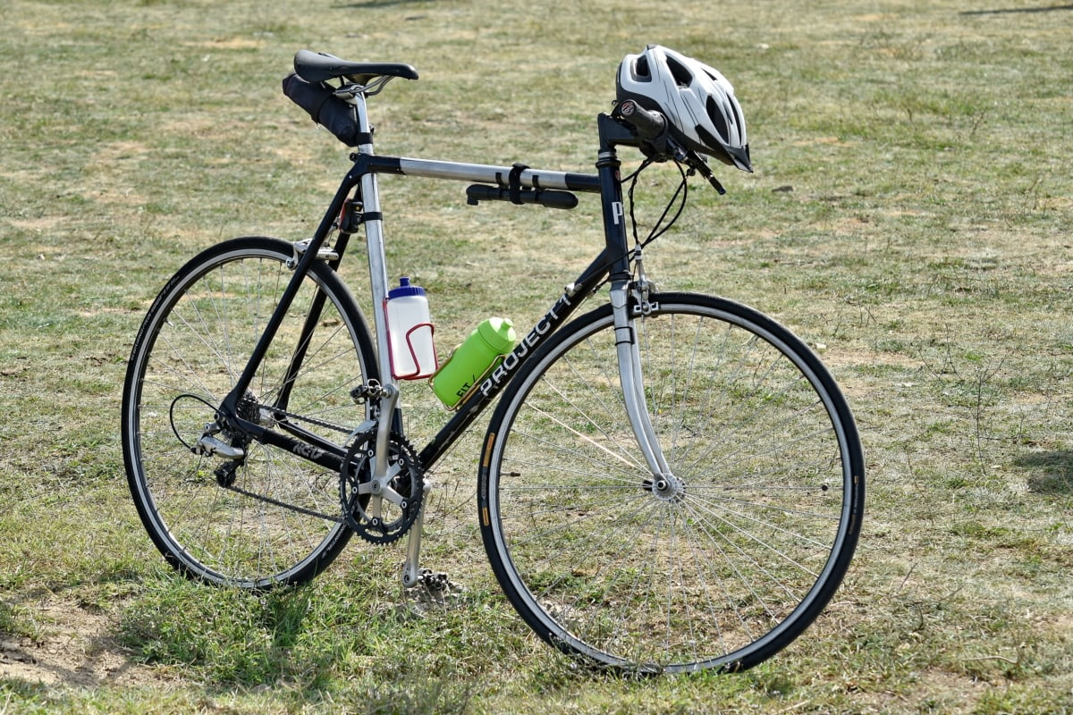 bicycle, equipment, helmet, mountain bike, object, pump, wheel, sport, grass, recreation