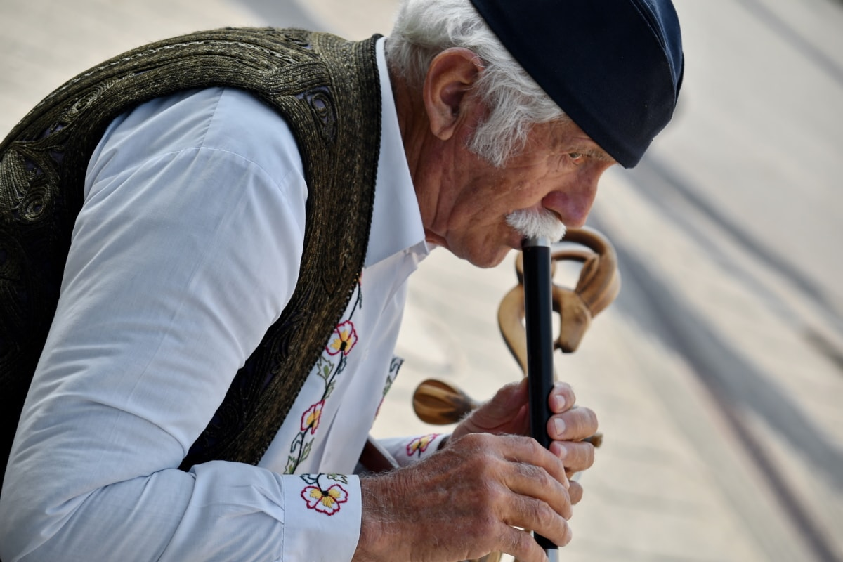 blow, carnival, festival, instrument, music, performance, traditional, man, street, elderly