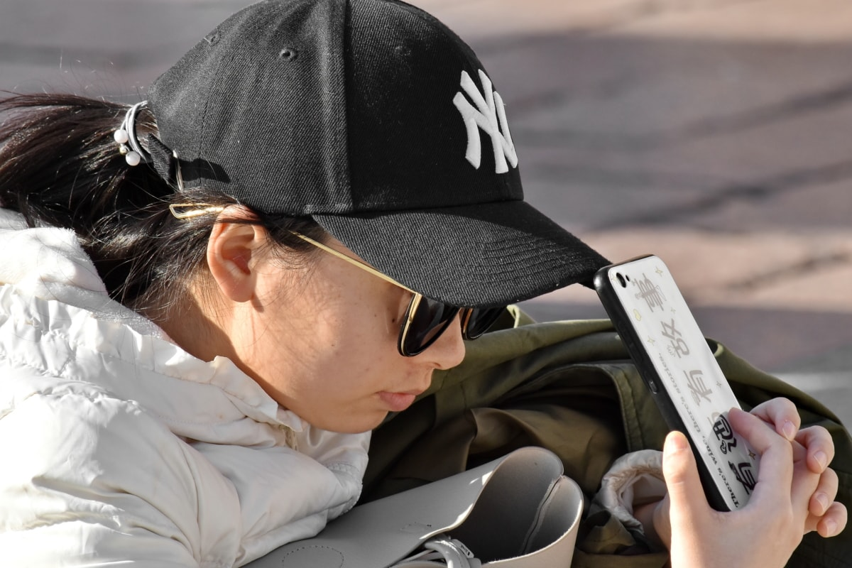 Asian, cellphone, girl, hat, side view, sunglasses, man, people, woman, outdoors
