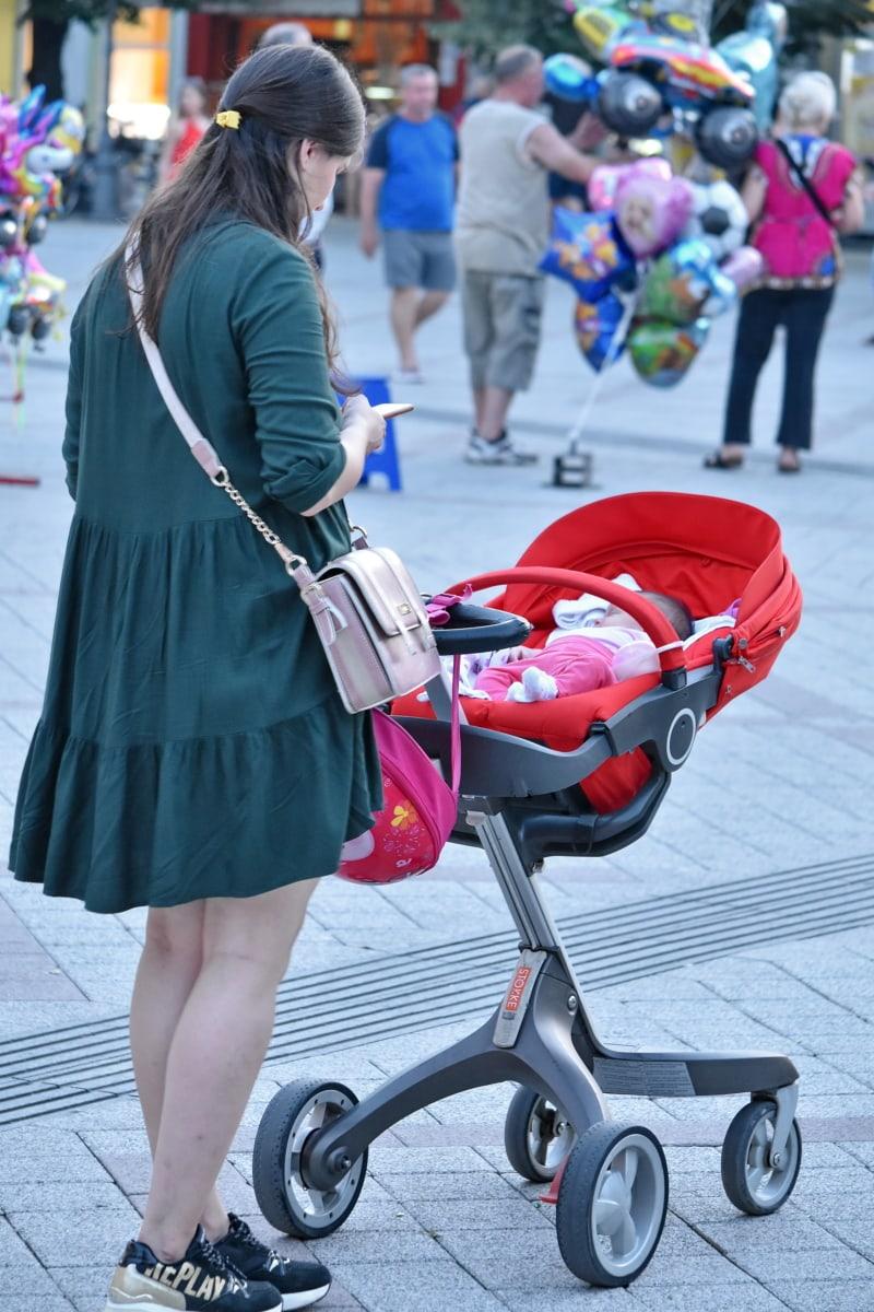 baby, cart, crowd, mobile phone, mother, motherhood, people, street, young woman, woman