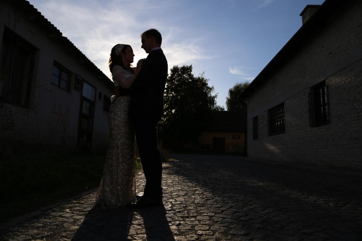affection, bride, darkness, groom, handsome, hug, pretty girl, shadow, side view, street