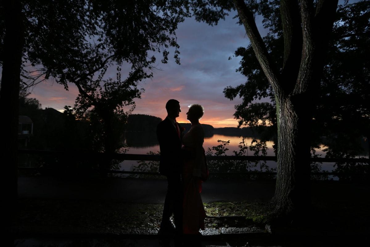 dress, hug, lakeside, man, night, pretty girl, shadow, side view, sunset, trees