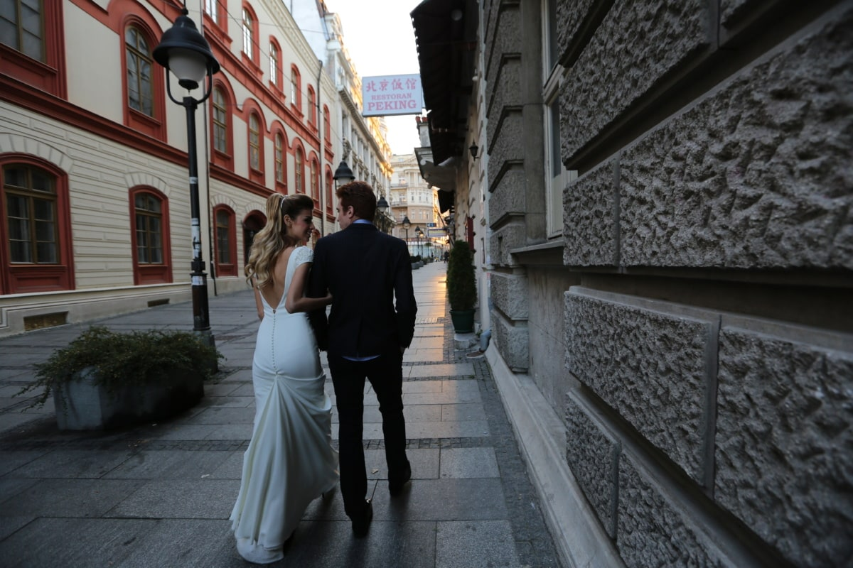 wife, wedding dress, husband, outfit, walking, suit, street, architecture, sidewalk, building