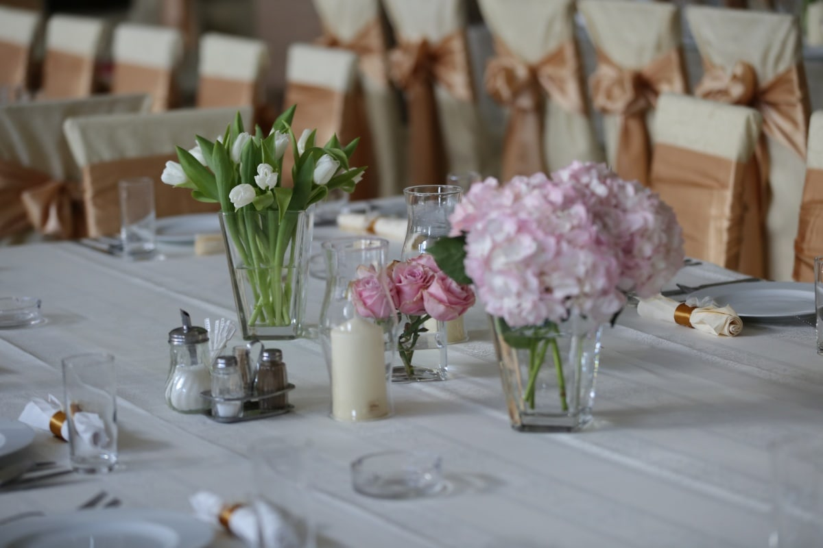 table, lunchroom, dining area, restaurant, tablecloth, cutlery, tableware, vase, bouquet, reception