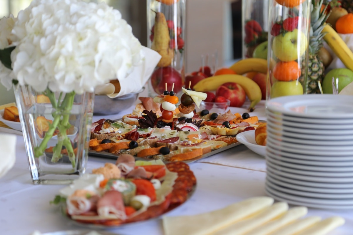snack, buffet, food, vase, tableware, tablecloth, table, fruit, dining area, lunchroom