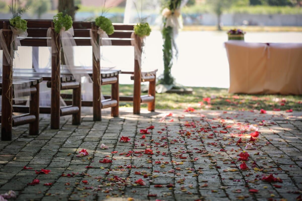 wedding venue, outdoors, floor, wedding, flowers, petals, bench, furniture, garden, architecture