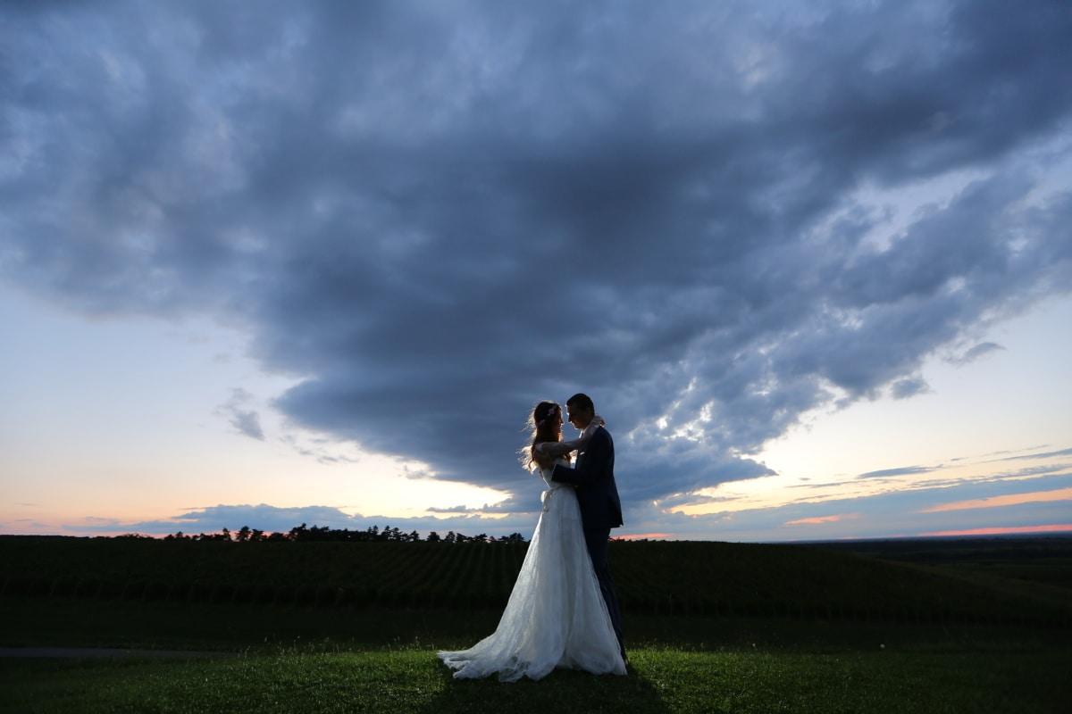 bad weather, storm, bride, hilltop, groom, hugging, sunset, dress, engagement, marriage