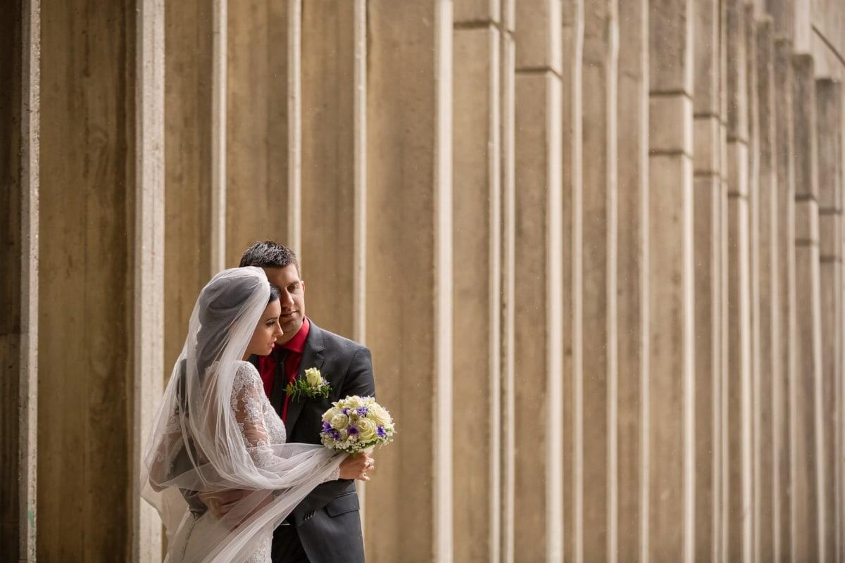 vue de côté, étreinte, amour, homme, femme, robe de mariée, mariage, bouquet de mariage, jeune marié, romance