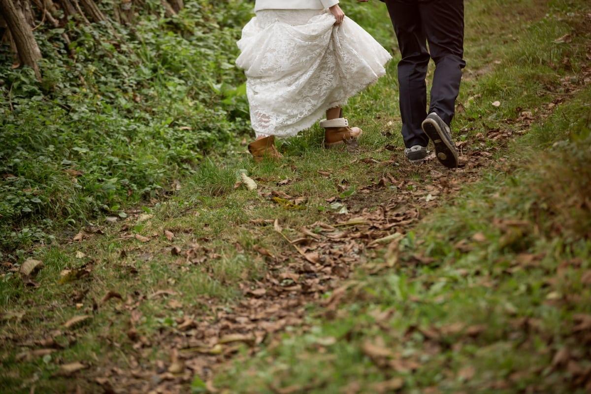slope, walking, shoes, mud, dress, pants, women, man, person, people