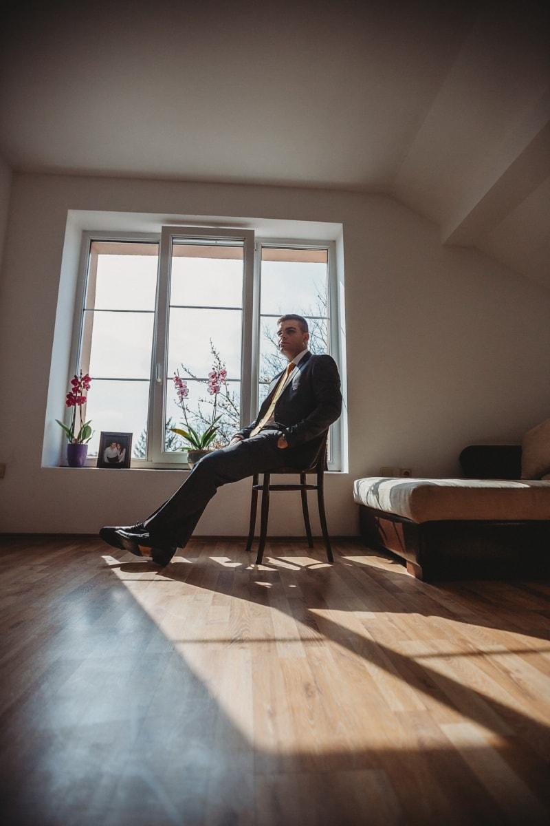 man, apartment, sitting, chair, suit, tuxedo suit, businessman, posing, indoors, interior