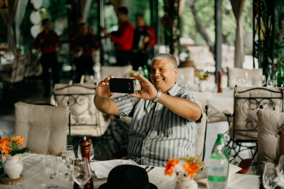 homme, souriant, cafétéria, restaurant, assis, téléphone portable, photographe, gens, rue, meubles