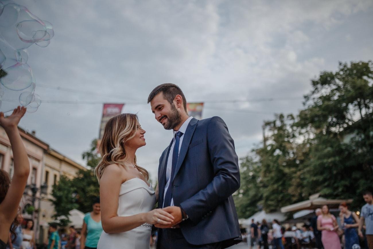 businessman, partners, pretty girl, embrace, street, hugging, spectator, crowd, businesswoman, wedding