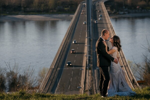 embrace, groom, love, bride, suspension bridge, urban area, cityscape, bridge, sunset, water