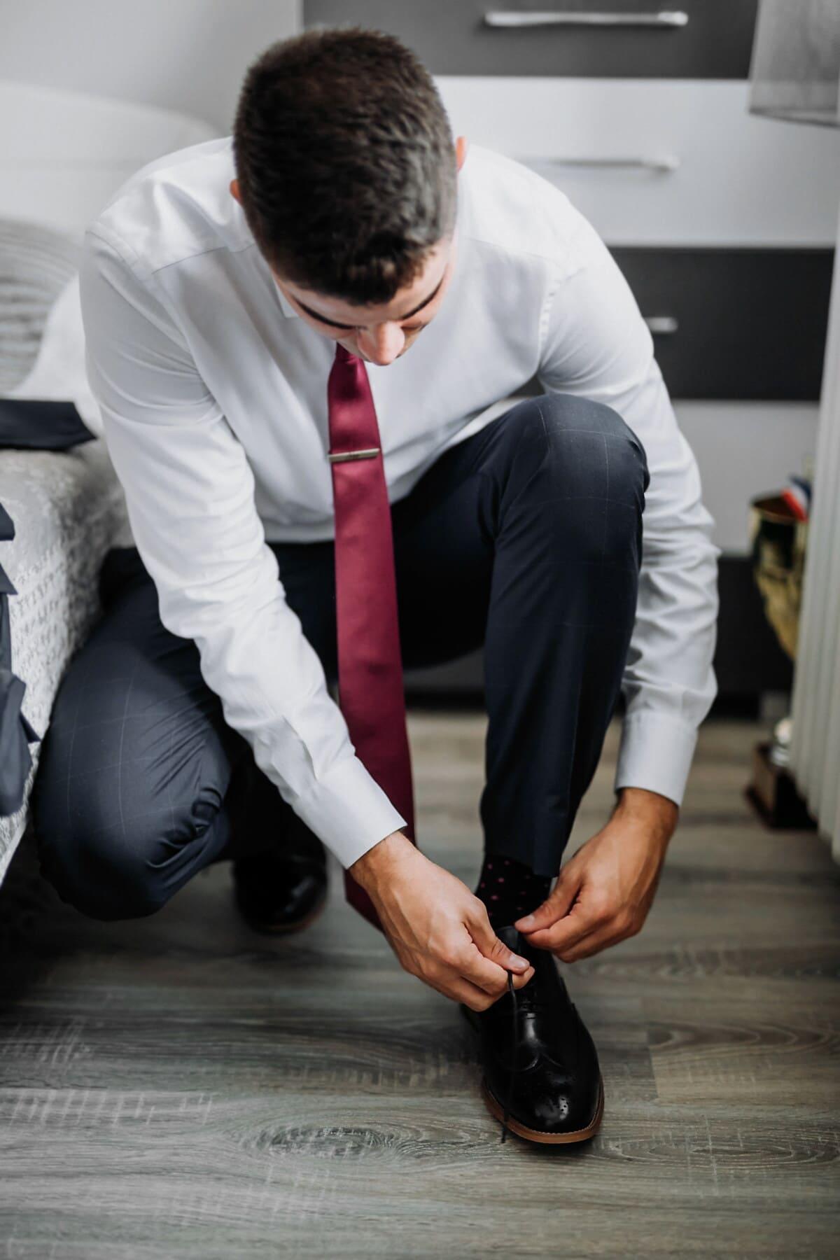 man, knee, floor, bedroom, shoes, tuxedo suit, tie, bed, shoelace, manager