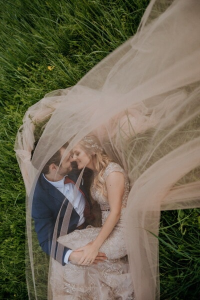 just married, kiss, groom, bride, veil, laying, grass, wedding, tent, love