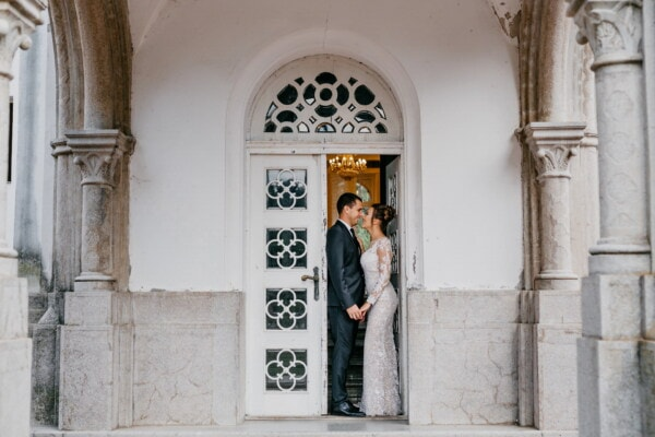 wife, husband, front porch, standing, front door, doorway, architecture, building, window, gothic