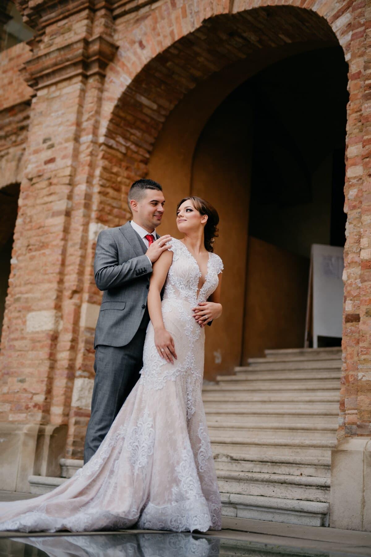 just married, bride, groom, standing, buildings, abandoned, stairway, shoulder, hand, dress