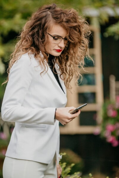 exitosa, elegante, traje, mujer de negocios, Morena, teléfono móvil, nina bonita, lápiz labial, lentes, peinado