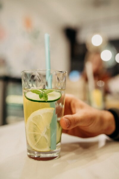 lemon, cold water, lemonade, drinking straw, beverage, drink, hand, glass, juice, cold
