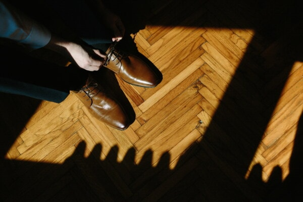 hands, shadow, shoelace, shoes, light brown, parquet, floor, hardwood, pants, tuxedo suit