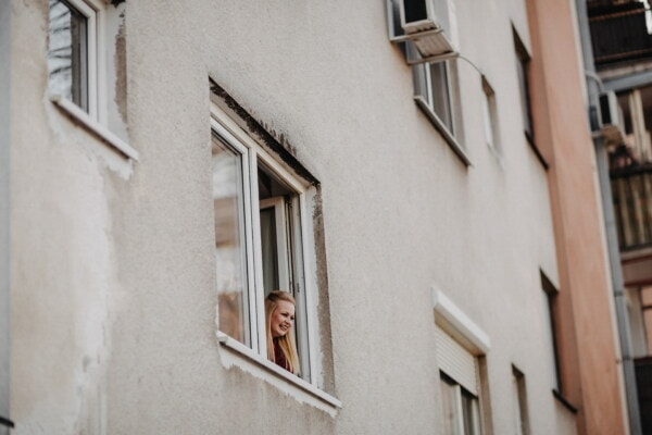 blonde hair, young woman, looking, window, facade, building, architecture, street, house, city