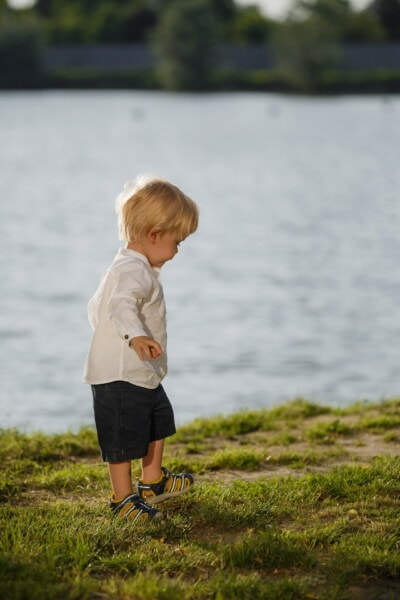 walking, blonde hair, toddler, side view, sneakers, shorts, child, happy, fun, water