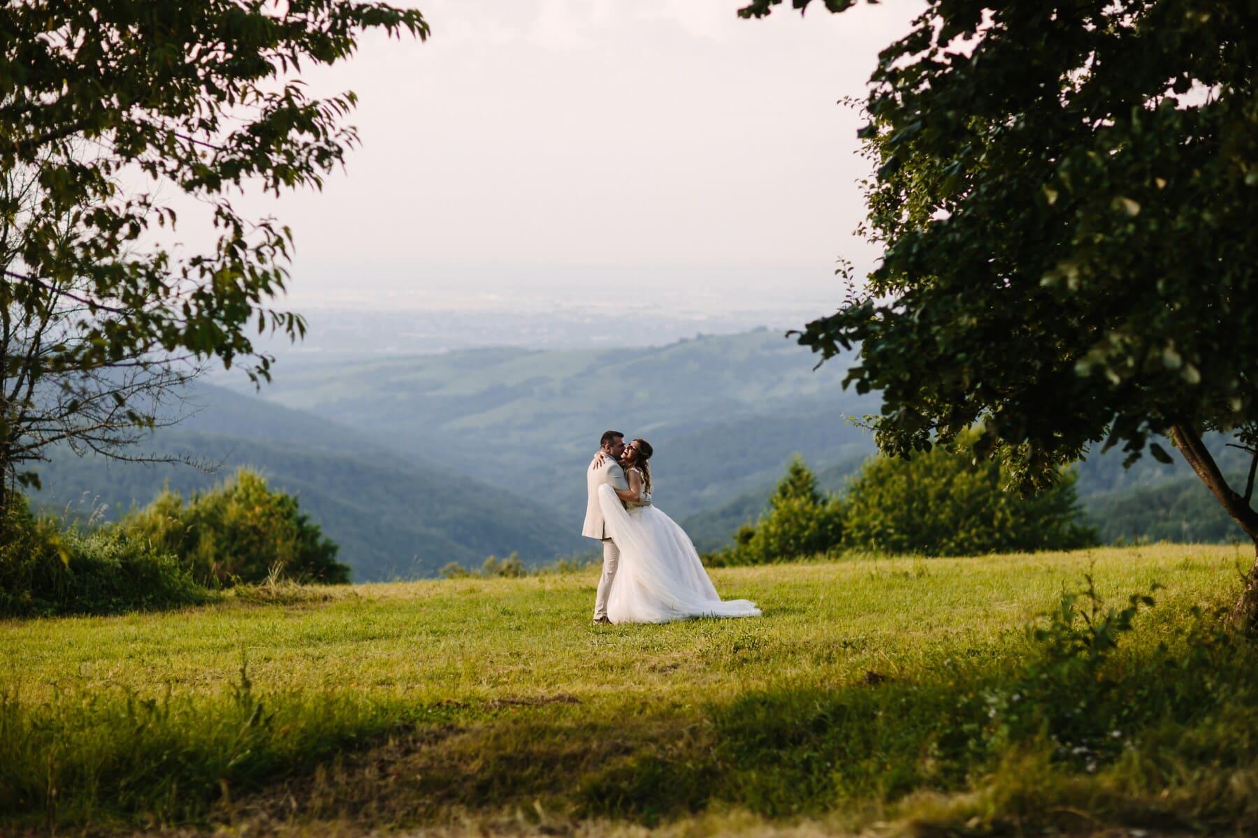 hugging, newlyweds, knoll, hillside, valley, hilltop, love, wedding, engagement, bride