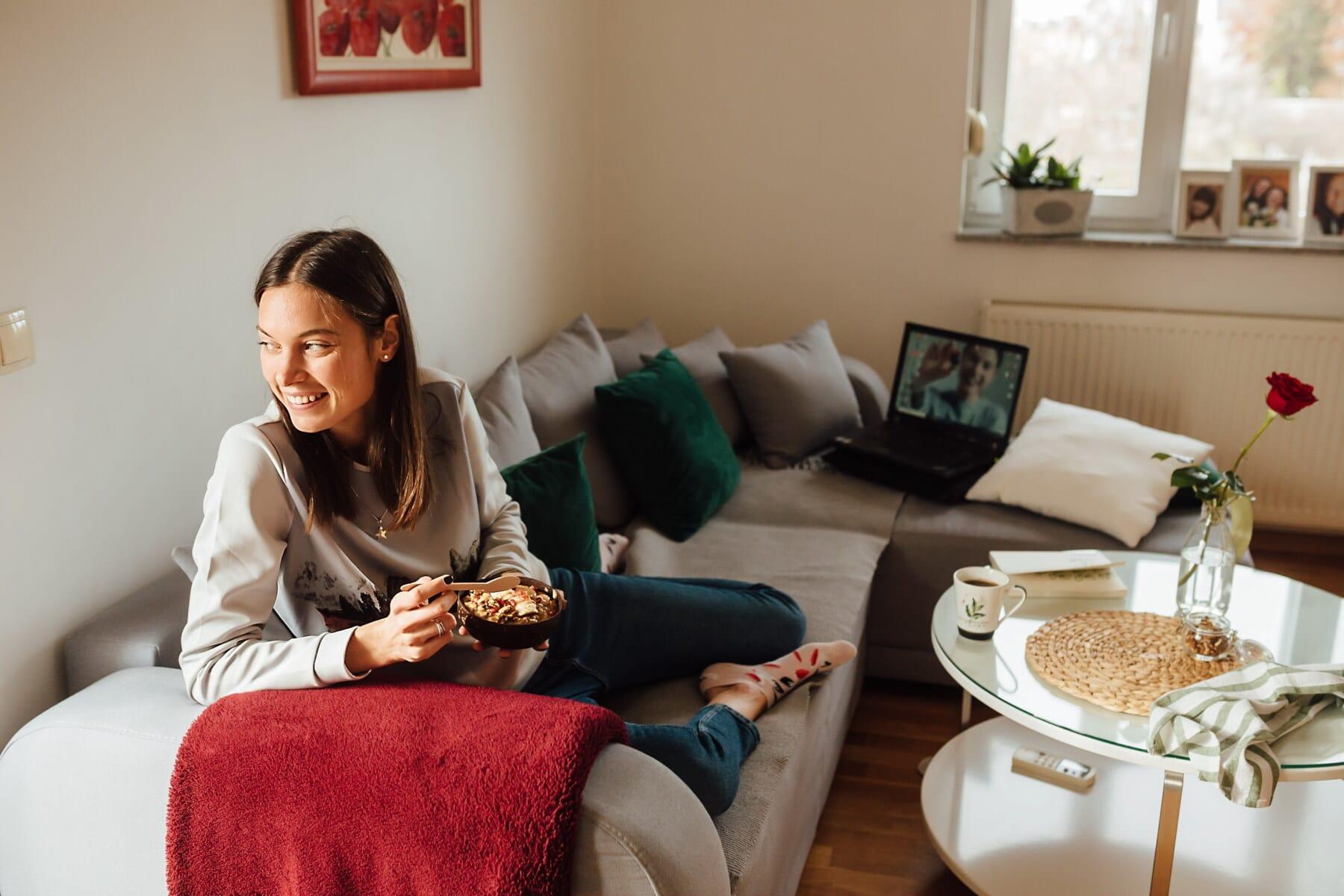 wanita muda, tersenyum, sarapan, Ruang tamu, relaksasi, sofa, gaya hidup, komputer laptop, Kamar, di dalam ruangan
