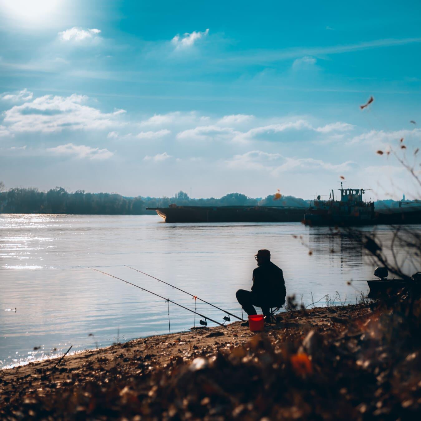 fisherman, fishing, sitting, fishing rod, riverbank, shadow, barge, cargo ship, lake, water