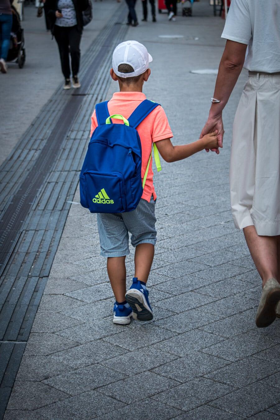 school child, school day, holding hands, mother, son, walking, urban area, street, people, child