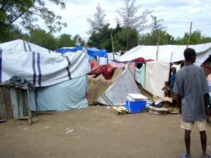 haitiano, el hombre, de pie, afuera, improvisada tienda de campaña, casas,
